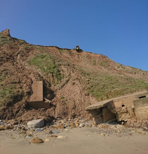 Cliffs at Cayton Bay with precarious WW2 building on cliff top.